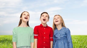 Amazed boy and girls looking up. Childhood, summer, emotion, friendship and people concept - happy amazed boy and girls looking up with open mouths over blue sky Royalty Free Stock Image