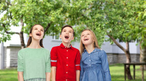 Amazed boy and girls looking up over backyard Stock Photography