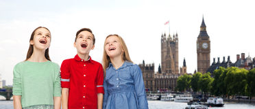 Amazed boy and girls looking up over london. Childhood, travel, tourism, friendship and people concept - happy amazed boy and girls looking up with open mouths Stock Photography