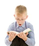 Amazed boy reading very interesting book. Portrait of amazed boy in eyeglasses reading very interesting book. Isolated on white background Royalty Free Stock Photo