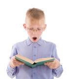 Amazed boy reading very interesting book. Portrait of amazed boy in eyeglasses reading very interesting book. Isolated on white background Royalty Free Stock Photo