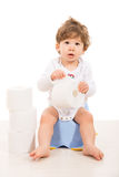 Amazed boy sitting on potty. And holding rolls of paper against white background royalty free stock photos