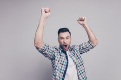 Amazed brunet guy with bristle in casual checkered shirt celebra. Ting victory of favorite sport team with raised arms, cams,  shouting, screaming, yelling with Stock Photos