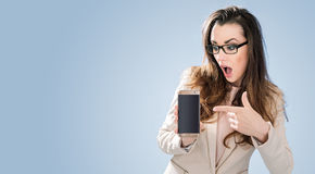 Amazed brunette lady poiting a cell phone. Amazed brunette woman poiting a cell phone Royalty Free Stock Photo