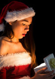 Amazed brunette in santa outfit opening a gift Stock Images