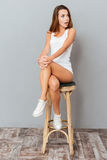 Amazed brunette woman sitting on the chair and looking away. Over gray background Stock Photo