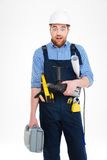 Amazed builder in helmet holding tool box, drill and blueprints Stock Photography
