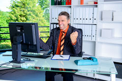 Amazed business man at his desk. Young amazed business man at his desk Royalty Free Stock Photo