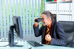 Amazed business man looking with binoculars at the screen Stock Photography