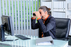 Amazed business man looking with binoculars at the screen Stock Image