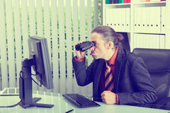 Amazed business man looking with binoculars at the screen. Young amazed business man looking with binoculars at the screen Stock Photography