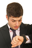 Amazed business man with watch. Amazed business man looking at his wrist watch isolated on white background Royalty Free Stock Photography