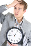 Amazed businessman in grey suit holding a clock. Over white Stock Image
