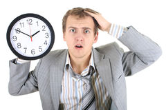 Amazed businessman in grey suit holding a clock. Over white Royalty Free Stock Photo