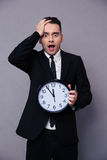 Amazed businessman holding wall clock Royalty Free Stock Images