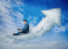 Cloud graph arrow. Amazed businessman looking at his laptop monitor while flying on a cloud graph arrow going up over a blue sky background. Financial concept stock image