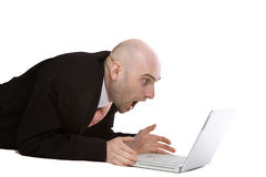 Amazed businessman using laptop. A view of a businessman, lying on the floor while using a laptop computer, appearing to be shocked or amazed and what he sees on Stock Photos