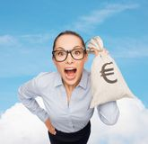 Amazed businesswoman holding money bag with euro Royalty Free Stock Photo