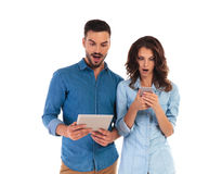 Amazed casual couple reading surprising things on their mobile d. Evices on white background Royalty Free Stock Images