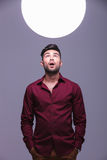 Amazed casual man  looking into a sphere of light. Amazed casual man with hands in pockets looking into a sphere of light Royalty Free Stock Image