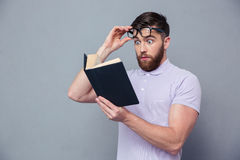Amazed casual man reading book. Portrait of amazed casual man reading book oer gray background Stock Image