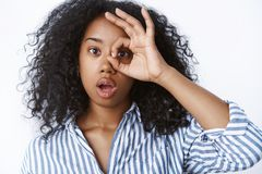 Amazed charming dark-skinned young millennial girl curly-haired open mouth wow sound showing okay ok gesture looking royalty free stock image