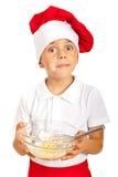 Amazed chef boy holding dough. Amazed chef boy with messy face of flour holding dough isolated on white background Stock Images