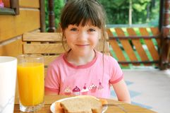 Amazed child girl has a breakfast outdoors. Smiling child girl has a healthy breakfast outdoors Royalty Free Stock Images