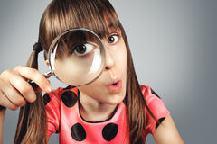 Amazed child girl looking through magnifying glass, searching co. Ncept stock photography
