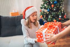 Amazed child holds present and looks at it. She keeps mouth opened. Girl wears Christmas hat. Adult supports her by stock images