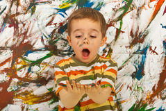 Amazed child looking at messy palms. Surprised child boy looking at his messy palms  against painted background Stock Photography