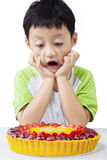 Amazed child looking at pie. Picture of funny little boy with amazed expression, looking at a delicious pie on the table Stock Photo