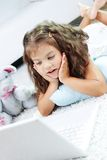 Amazed child. Portrait of lovely girl looking at laptop screen with surprise Stock Image
