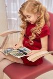 Amazed child reading fashion magazine. Surprised little girl. How media influences children Stock Photo