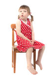 Amazed child sitting on a chair. Surprised little baby girl isolated on white background Royalty Free Stock Photos