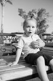 Amazed child sitting with two oranges on bench. Amazed child or small little baby boy sitting with two oranges on bench on sunny day in park. Kid with blond hair Stock Photos
