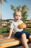 Amazed child sitting with two oranges on bench. Amazed child or small little baby boy sitting with two oranges on bench on sunny day in park. Kid with blond hair Stock Images