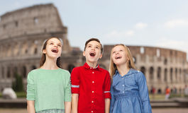 Amazed children looking up over coliseum in rome. Childhood, travel, tourism, emotions and people concept - happy amazed boy and girls looking up with open Royalty Free Stock Photos