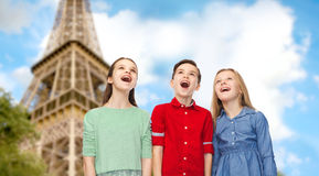 Amazed children looking up over eiffel tower. Childhood, travel, tourism, friendship and people concept - happy amazed boy and girls looking up with open mouths Royalty Free Stock Photo