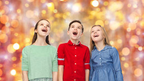 Amazed children looking up over holidays lights. Childhood, charistmas, holidays, party and people concept - happy amazed boy and girls looking up with open Royalty Free Stock Photography