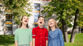 Amazed children looking up over summer campus. Childhood, education, friendship and people concept - happy amazed children looking up with open mouths over Royalty Free Stock Image