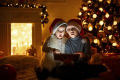 Amazed children using tablet near Christmas tree. Amazed boy and girl in Christmas hats sitting near brightly decorated Christmas tree and using tablet Stock Photos