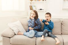 Amazed children watching TV at home. Surprised children watching movie at home, brother and sister having rest without parents, copy space Royalty Free Stock Photos