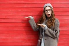 Amazed chocou a jovem mulher que está e que guarda o copyspace na palma Foto de Stock Royalty Free