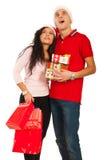Amazed Christmas couple looking up. Amazed Christmas couple holding presents and looking up to copy space isolated on white background Royalty Free Stock Image