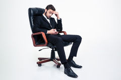 Amazed concentrated businessman sitting in office chair and using smartphone Royalty Free Stock Photos