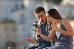 Amazed couple checking smart phone in a town. Amazed couple checking smart phone content sitting on a ledge in a town stock image