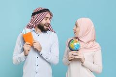 Amazed couple friends arabian muslim man wonam in keffiyeh kafiya ring igal agal hijab clothes isolated on blue