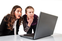 Amazed couple on line with a laptop Royalty Free Stock Image