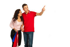 Amazed couple looking away. Amazed couple at shopping looking away and men pointing to copy space isolated on white background Royalty Free Stock Photography